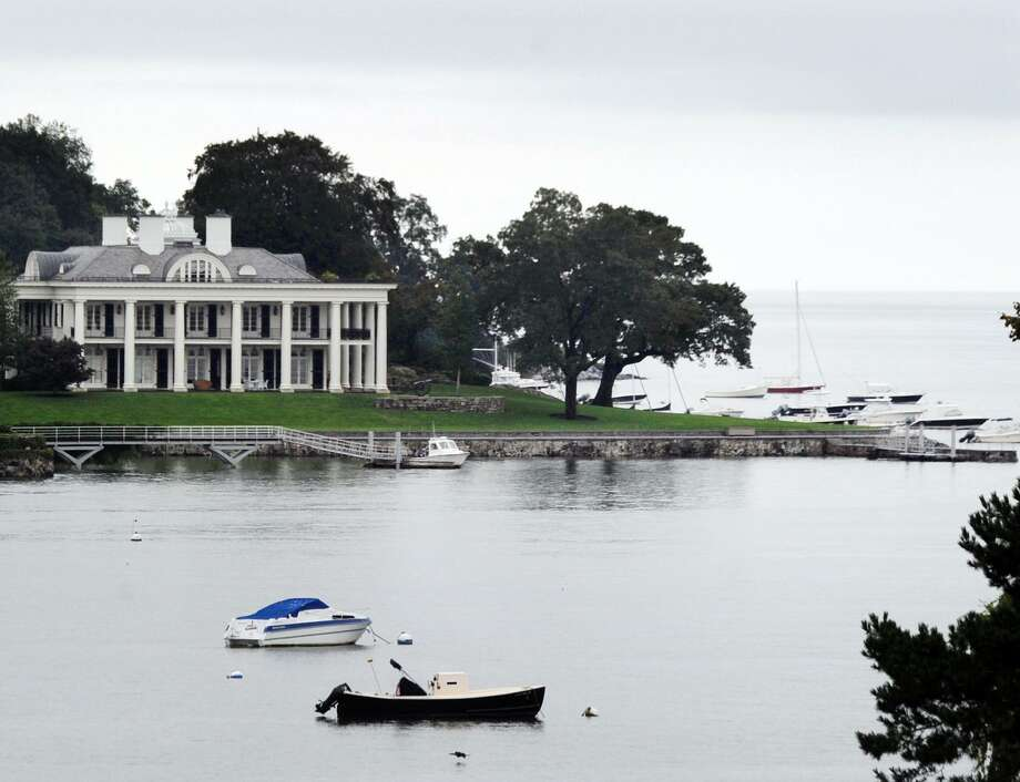 With the Paul Tudor Jones mansion visible in the backgound, boats can be seen moored in Byram Harbor off the coast of Greenwich, Conn., Tuesday, Sept. 11, 2018. With hurricane Florence, a category 4 storm with sustained winds of 130 mph, approaching the east coast of the United States in the area of the Carolinas, the harbormasters in Connecticut are warning boaters that now is the time to prepare and shore-up boats. Photo: Bob Luckey Jr. / Hearst Connecticut Media / Greenwich Time