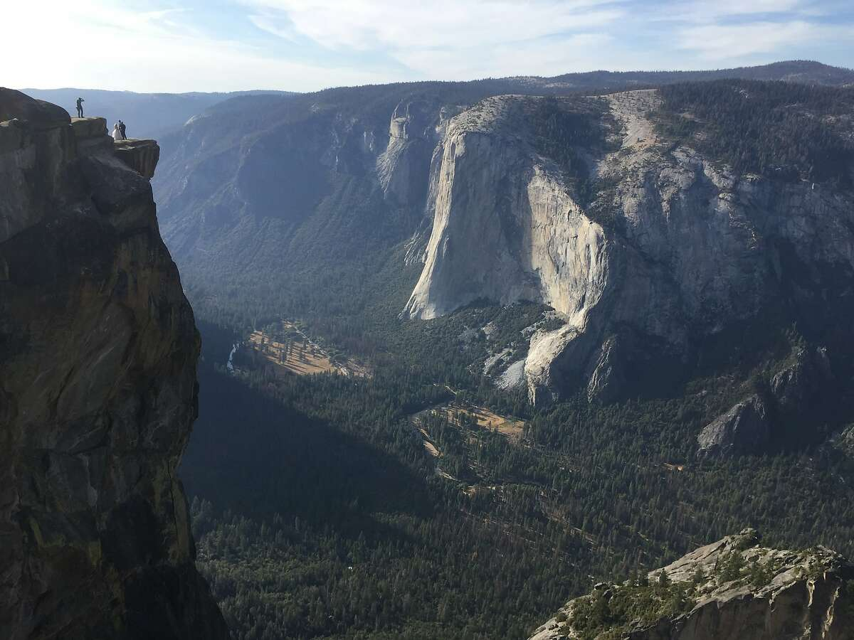 This file photo shows a couple getting married at Taft Point in California's Yosemite National Park on Sept. 27, 2018. The viewpoint overlooks Yosemite Valley, including El Capitan, a popular vertical ascent for rock climbers across the globe. On Thursday, two visitors apparently fell to their deaths from the lookout, officials said.