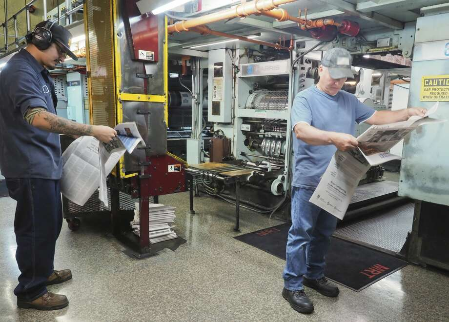 Jaime Martinez and Sergio Ramirez grab copies off the press to check color, ink coverage and registration 10/24/18 evening during the last printing of the Midland Reporter-Telegram on our press. Tim Fischer/Reporter-Telegram Photo: Tim Fischer/Midland Reporter-Telegram