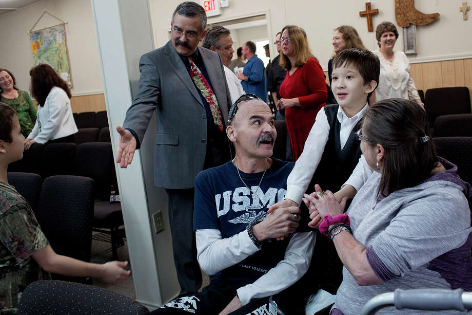 "Gunny Macias and his wife, Jennifer, meet with fellow parishioners a few months after his return to the church. Seriously wounded in the attack, Gunny, a Marine veteran, used a walker and still was connected to tubes on his first visit back. ""I felt all the embarrassment, and the pain, and all that stuff just went away when I got to church. Just went away, and melted away, and it still does."" / Lisa Krantz/San Antonio Express-News"