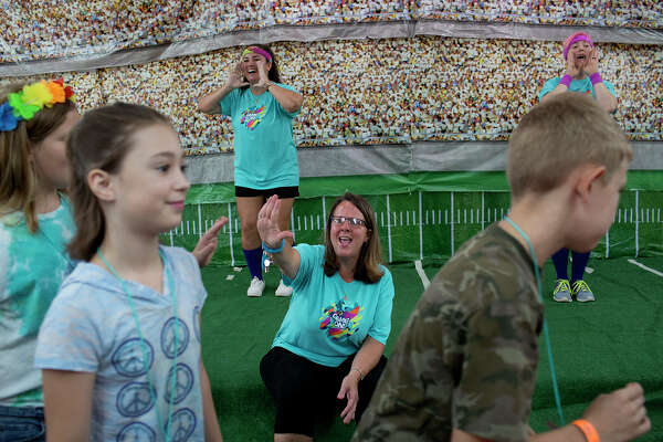 Sherri Pomeroy, center, with Britteny Martinez, left, and Colbey Workman, get Vacation Bible School students singing and dancing in an event at the church.