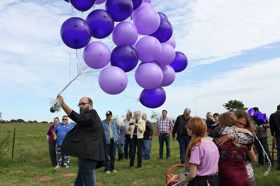 Kaleb Pomeroy carries balloons to be released at the gravesite of his sister, Annabelle, on what would have been her 15th birthday. Their mother, Sherri Pomeroy, embraces Kaleb's daughter, Amanda, 10. / Lisa Krantz/San Antonio Express-News