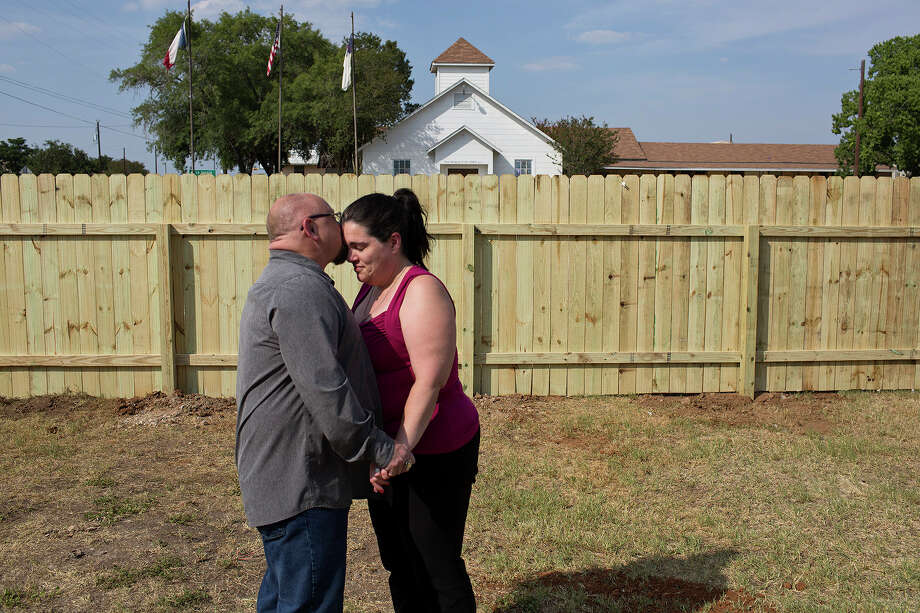 Kathleen Curnow and her husband, Fred Curnow, celebrate completion of the fence built around her house by youth missionaries from East Saugatuck Church of Holland, Michigan. She had heard the gunfire from her house and saw Devin Kelley flee from the church after the massacre. / Lisa Krantz/San Antonio Express-News