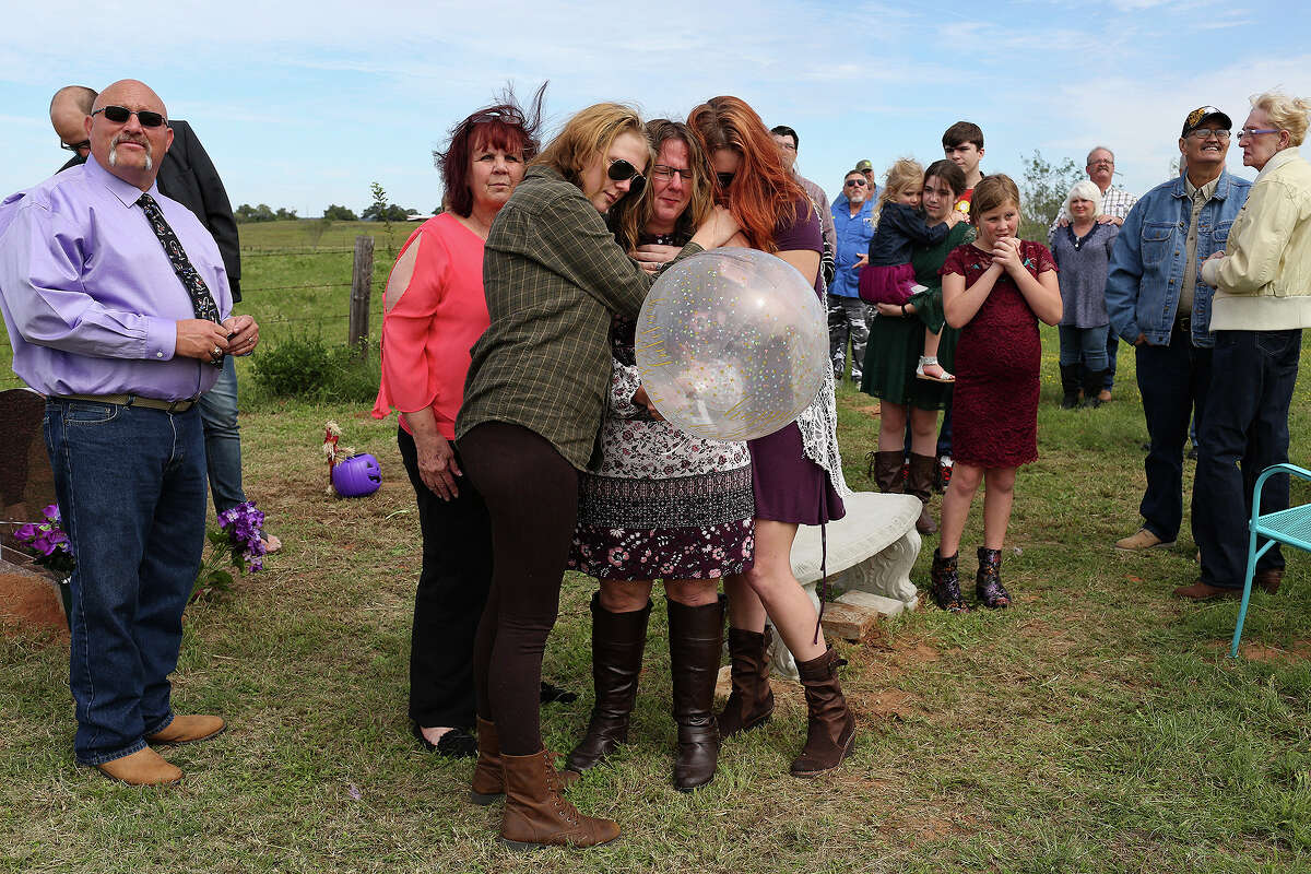 Sherri Pomeroy is embraced by her daughter-in-law, Chelsi Pomeroy, left, and her daughter, Kandi Pomeroy, as Sherri holds a balloon to release in honor of what would have been the 15th birthday for her slain daughter, Annabelle.