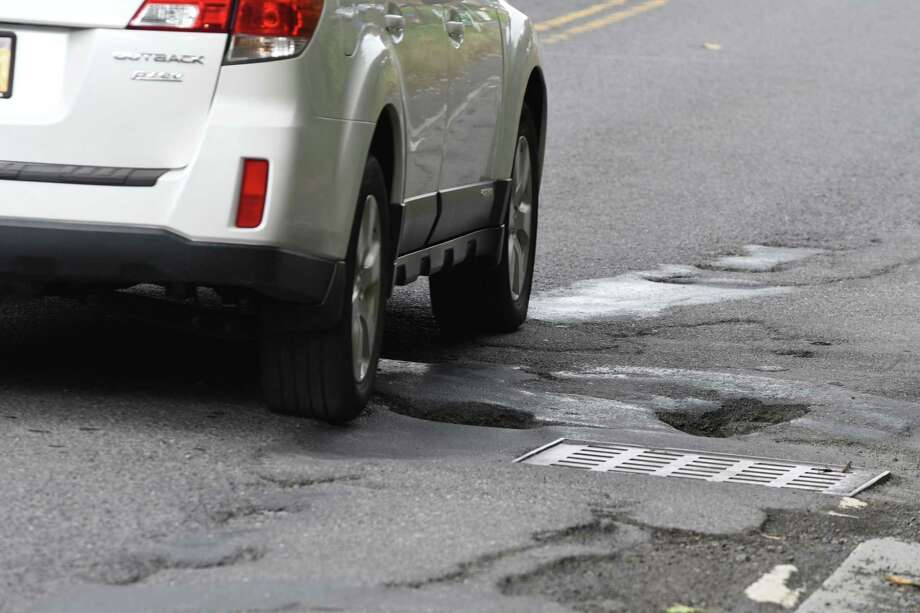 A car navigates a pothole-strewn section of Hackett Blvd. between Holland Ave. and Crown Terrace on Thursday, Oct. 25, 2018, in Albany, N.Y. (Will Waldron/Times Union) Photo: Will Waldron, Albany Times Union