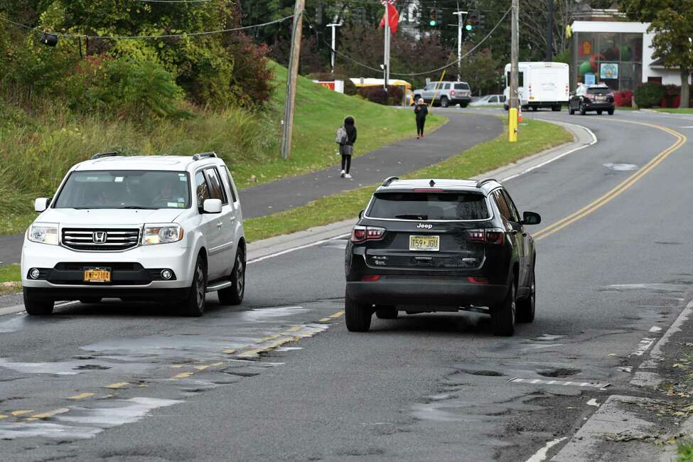 Vehicles navigate a pothole-strewn section of Hackett Blvd. between Holland Ave. and Crown Terrace on Thursday, Oct. 25, 2018, in Albany, N.Y. (Will Waldron/Times Union)