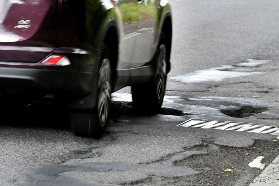 A car navigates a pothole-strewn section of Hackett Blvd. between Holland Ave. and Crown Terrace on Thursday, Oct. 25, 2018, in Albany, N.Y. (Will Waldron/Times Union)