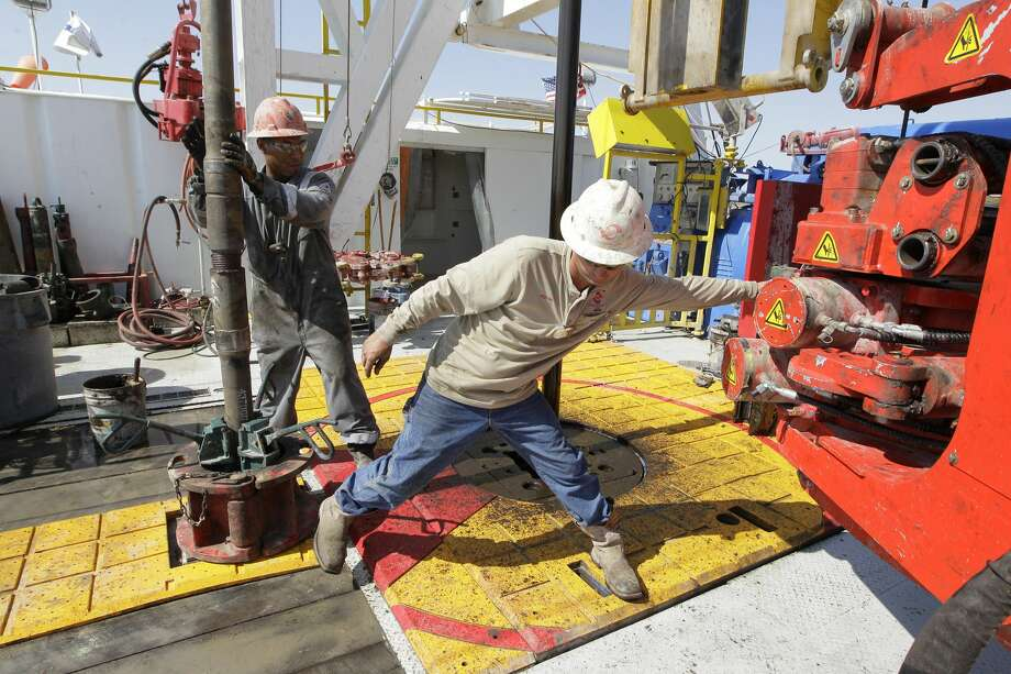 Demarcus Skinner (left) and Driller Jaylon Bolton work on Scandrill's oil rig named Scan Pride Wednesday, June 28, 2017, in Orla, Texas. Scandrill has found one way to deal with the excess gas, they use it to power the rigs that drill for oil. ( Steve Gonzales  / Houston Chronicle ) Photo: Steve Gonzales/Houston Chronicle