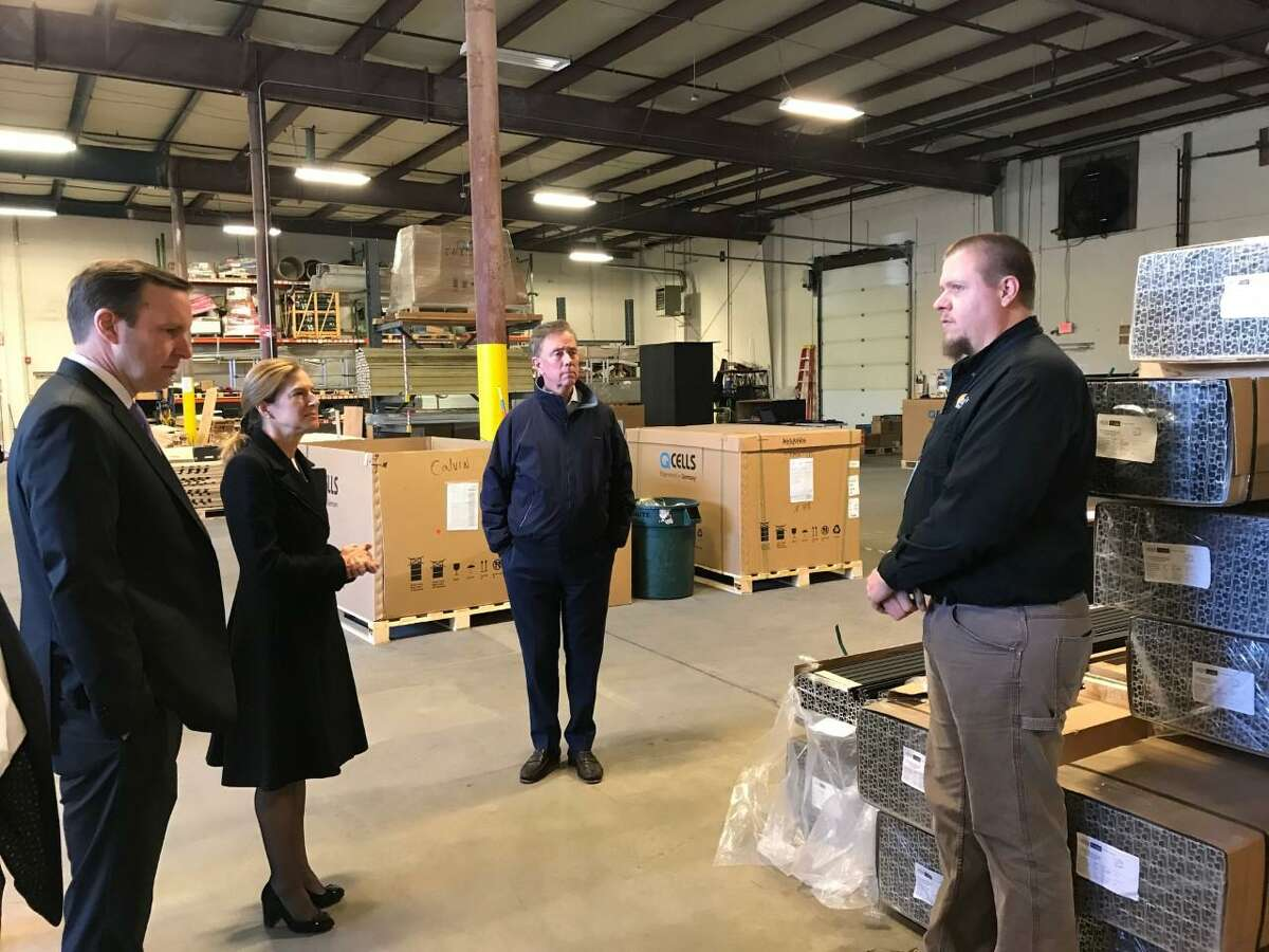 U.S. Sen. Chris Murphy, D-Connecticut, Lt. Gov. Candidate Susan Bysiewicz and Ned Lamont, the Democratic gubernatorial candidate listen as an employee of Trinity Solar explains the operations at the company's Cheshire warehouse Thursday.