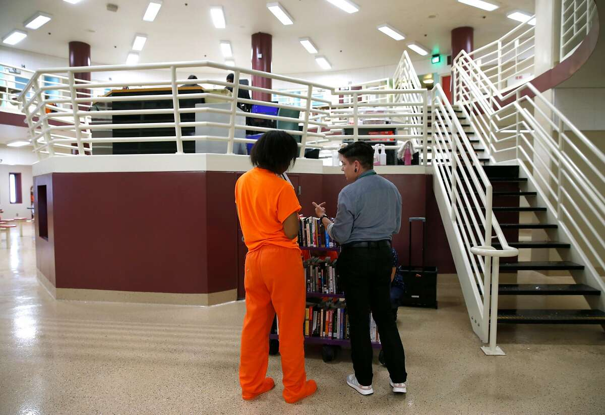 Librarian Jeanie Austin (right) helps an inmate select a book at the county jail on Seventh Street in San Francisco, Calif. on Tuesday, Oct. 2, 2018. The San Francisco Public Library provides a new service for inmates by bringing books to the jail.