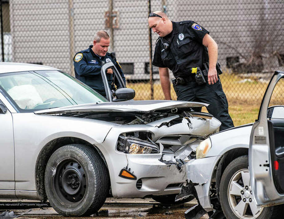 Wood River police officer Chris Alfaro and Alton officer Brian Brenner check out the Dodge Charger that had been reported stolen before fleeing an attempted traffic stop and crashing into another vehicle Thursday afternoon in Wood River. Photo: Nathan Woodside | The Telegraph