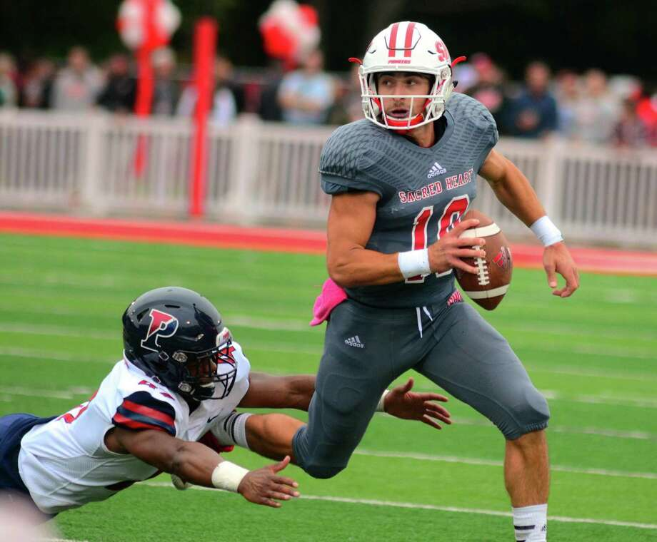 Sacred Heart University QB Kevin Duke tries to evade a tackle by Penn's Nick Miller during college football action in Fairfield, Conn. on Saturday Oct. 6, 2018. Photo: Christian Abraham / Hearst Connecticut Media / Connecticut Post