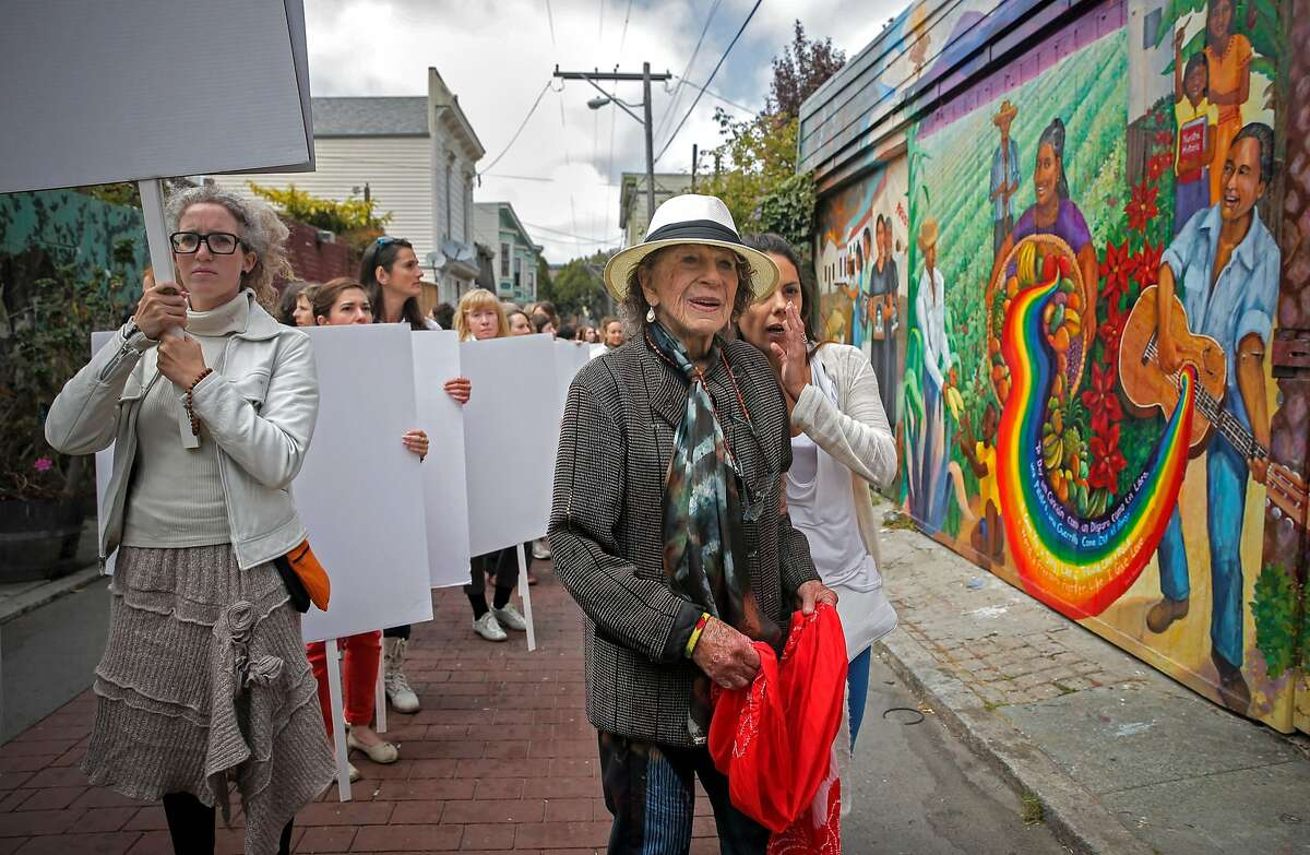 """Anna Halprin (c) in the Mission district in 2015, with dancers doing her """"Blank Placard Dance"""" march."""