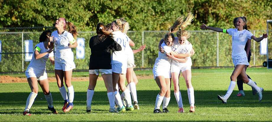 The Darien girls soccer team celebrates one of its two goals during the opening 90 seconds of overtime as the eighth-seeded Blue Wave stunned top-seeded Staples 2-0 at Loeffler Field in Westport on Thursday. Photo: John Nash / Hearst Connecticut Media