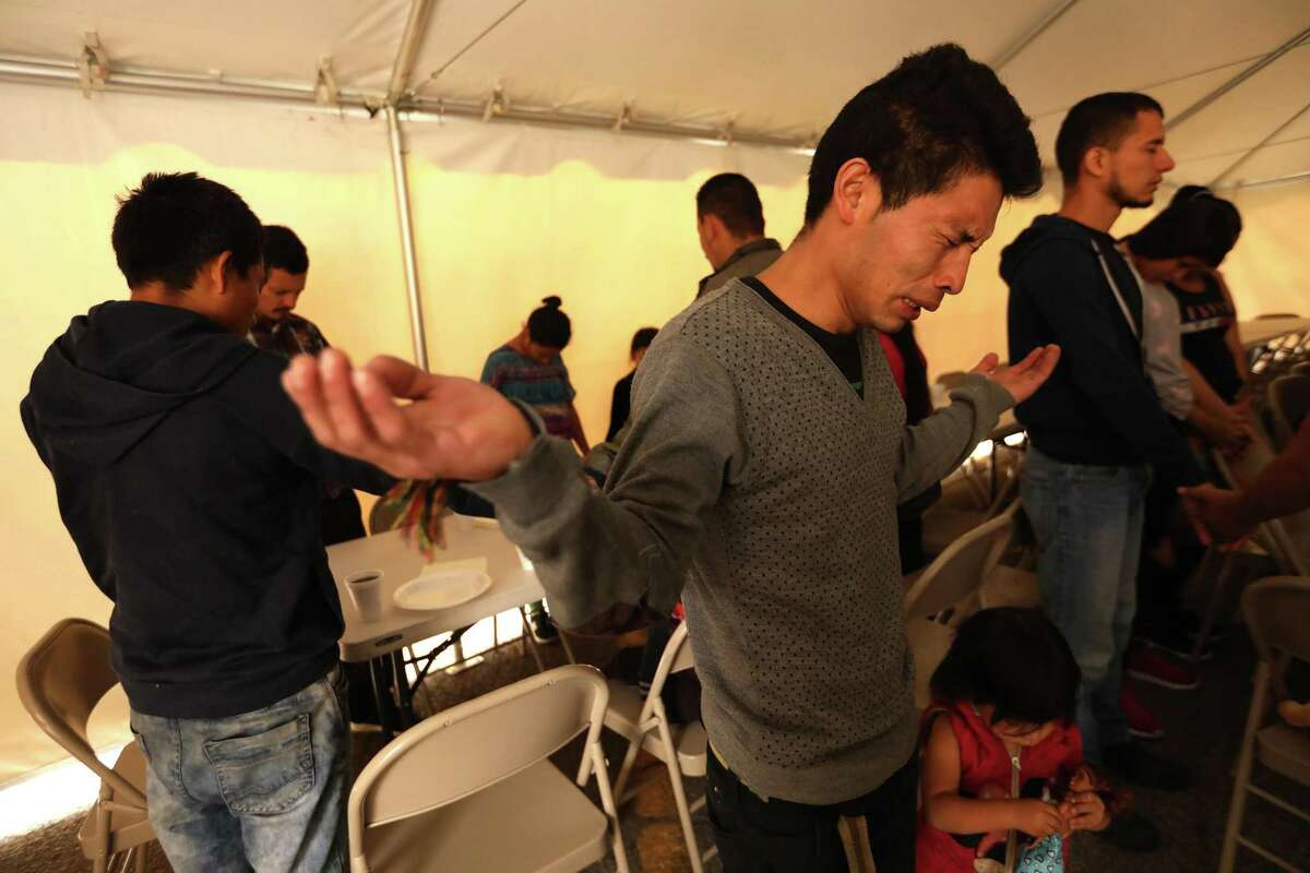 Victor Joel Fuentes Godinez, 25, from Honduras, becomes emotional while praying before lunch in a makeshift tent in the parking lot of an El Paso, Texas, motel on October 23, 2018.