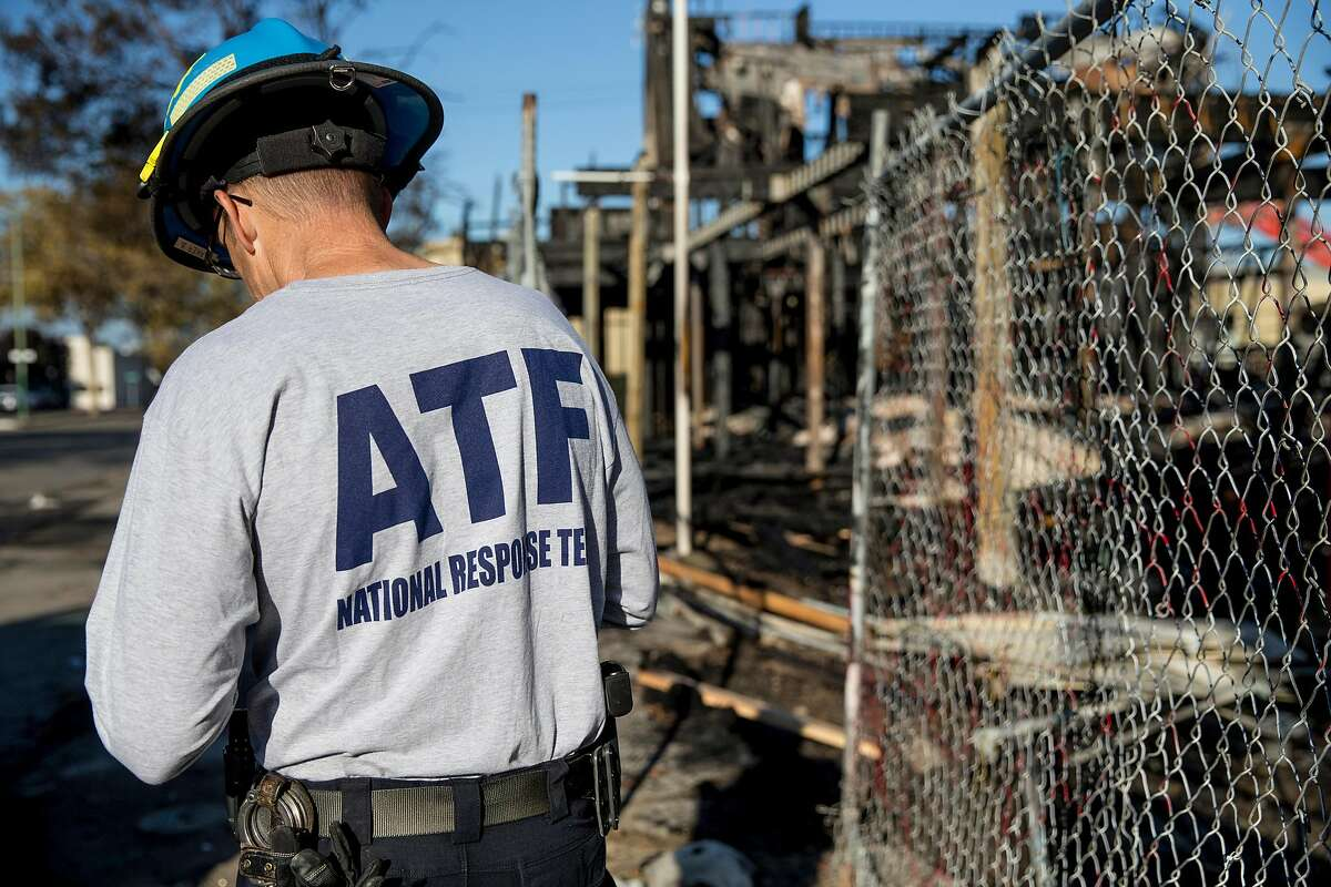 ATF agent Brian Parker walks with local construction workers as he asseses the scene where a massive blaze destroyed six apartment buildings in different phases of construction near West Grand Avenue and Filbert Street in Oakland, Calif. Wednesday, Oct. 24, 2018.
