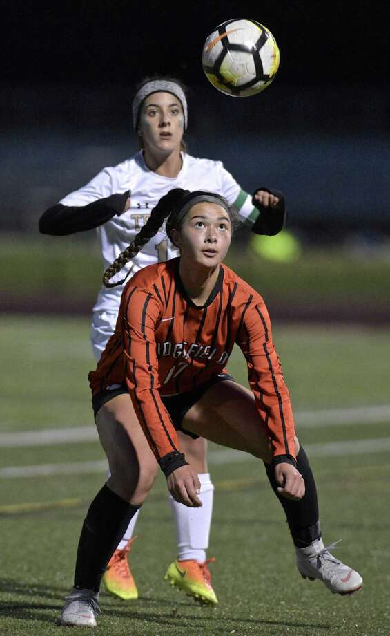 Ridgefield's Rasha Riek (17) keeps her eyes on the ball ahead of Trumbull's Jessica Esposito (13) in the FCIAC girls soccer game between Trumbull and Ridgefield high schools, Thursday night, October 25, 2018, at Ridgefield High School, Ridgefield, Conn. Photo: H John Voorhees III / Hearst Connecticut Media / The News-Times