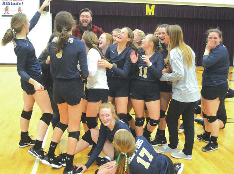 The Father McGivney girls' volleyball team celebrates with the championship plaque after beating Metro-East Lutheran in three games on Thursday in the title match of the Class 1A Mount Olive Regional. Photo: Scott Marion/Intelligencer