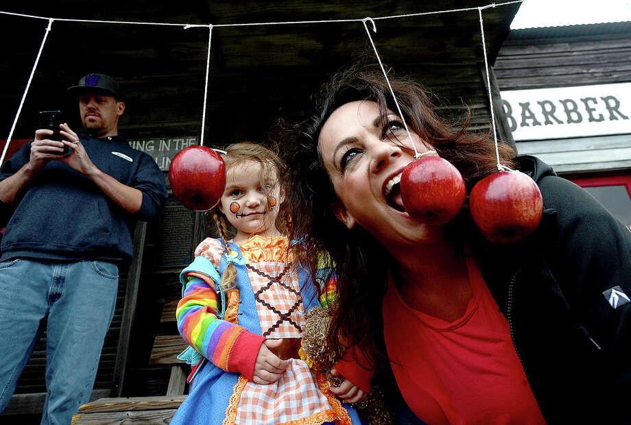 Zoey Odom watches as Athena Hislop tries to show her how to bob for an apple at the annual Spindletop Spookfest at the Spindletop/Gladys City Boomtown Museum.  Photo taken Thursday, October 25, 2018 Kim Brent/The Enterprise Photo: Kim Brent/The Enterprise