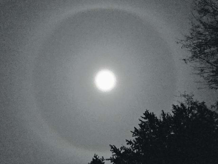 The full moon casts a halo that seems to fill the sky.