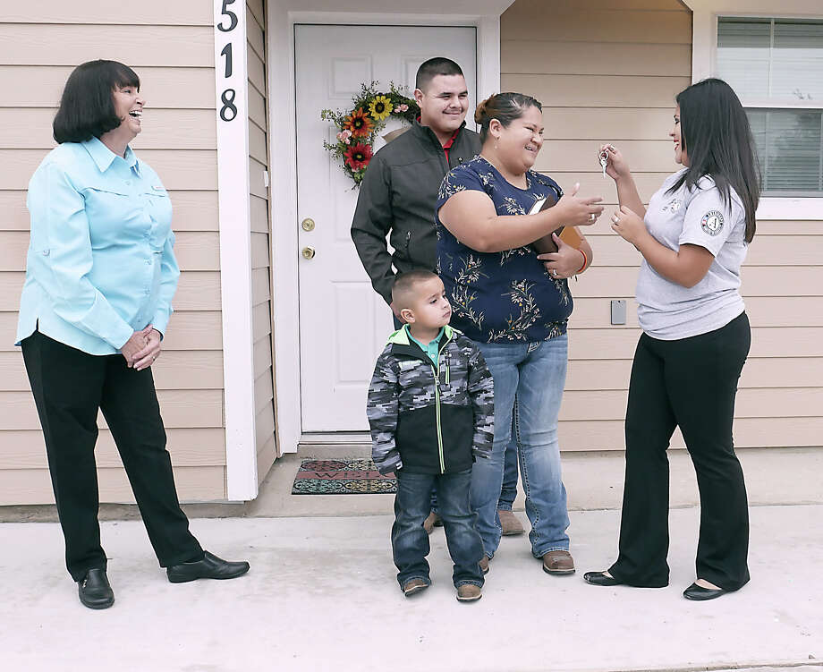 Erica de Luna, her husband Osiel Gutierrez and son Osiel Jr., react as they are presented with the keys to their new home by Habitat for Humanity/AmeriCorps Construction Crew Leader, Kimberly Mata, Thursday, October 25, 2018. Habitat for Humanity Laredo Executive Director Carol Sherwood looks on. The homeowners have been working hard to fulfill all of the requirements for Habitat Home Ownership, including putting in over 500 sweat equity hours. Photo: Cuate Santos, Laredo Morning Times / Laredo Morning Times