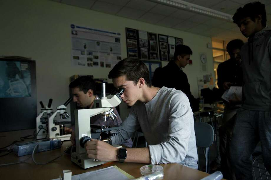 Stamford High School senior Ryan Hoak, 17, looks into a microscope to study yeast samples inside Stamford High School. The Board of Education's teaching, learning and community committee plans to discuss the proposal for Stamford and Westhill high schools Tuesday night. Photo: Michael Cummo / Hearst Connecticut Media / Stamford Advocate
