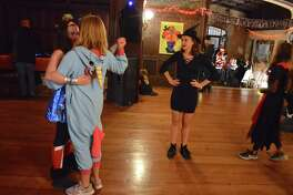 Hoping to warm up the dance floor are, from left, volunteers Anne Jessen, Eve Johansson, and Sydney Haydu, all 14 of New Canaan, at the 6th annual Halloween Witches Ball at Waveny House, Friday, Oct. 19, 2018, in New Canaan, Conn.