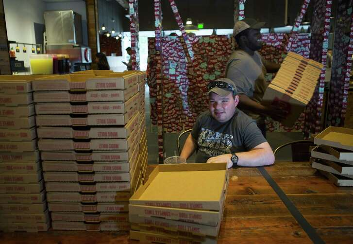 Aaron Glick folds pizza boxes at his part-time job at the MOD Pizza West Galleria location, Thursday, June 21, 2018 in Houston. Glick, who attends the Monarch School and Institute's Life Academy, started the job, his first, a little more than a year ago. ( Mark Mulligan / Houston Chronicle )