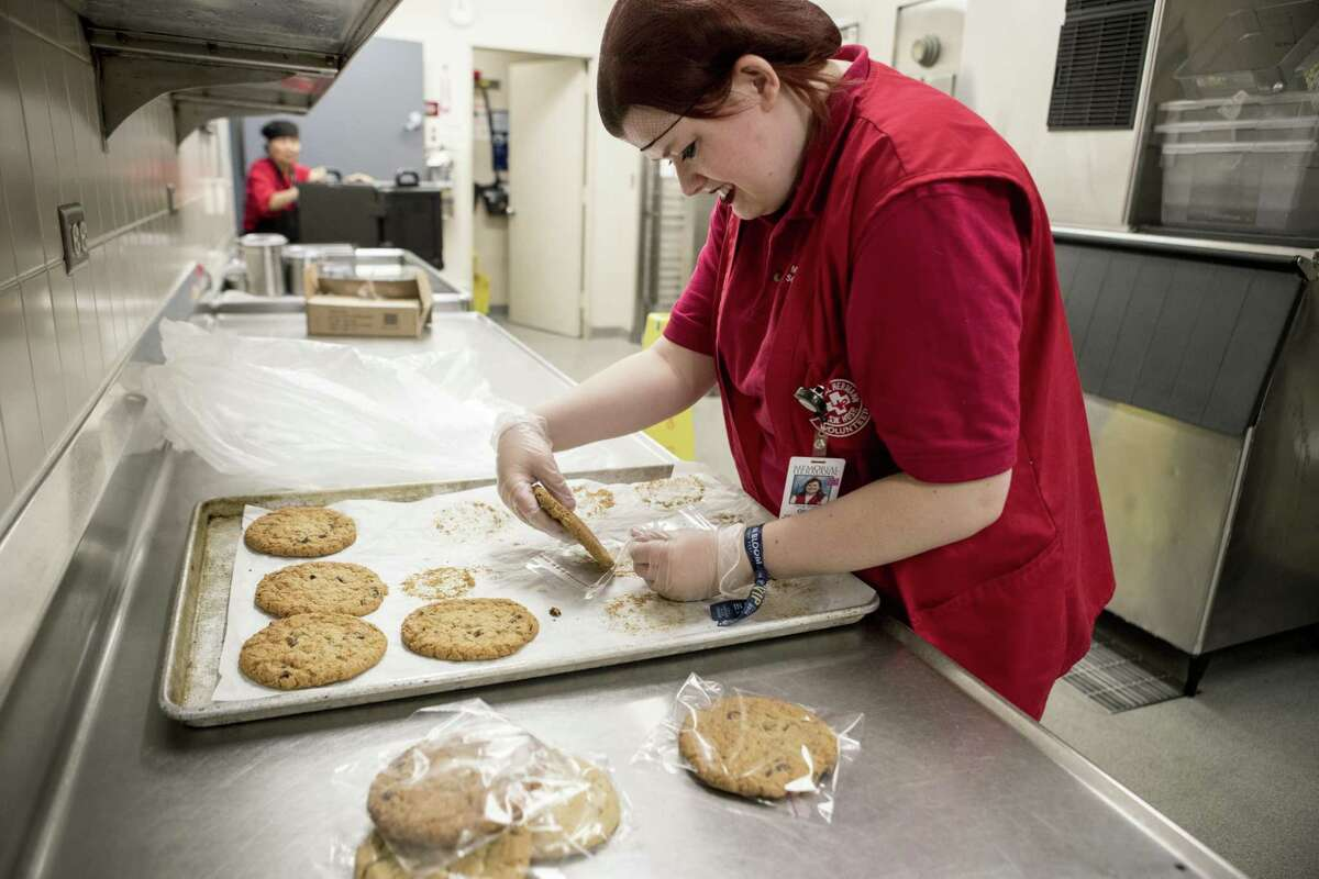 Olivia Shanks packages cookies in the cafeteria at Memorial Hermann Hospital Southwest on Tuesday, May 15, 2018, in Houston. Social Motion Skills is a nonprofit that offers a job-readiness internships to young adults with autism and similar special needs to transition into a work setting. It partners with the hospital to teach interns in the food service and cafeteria area. ( Brett Coomer / Houston Chronicle )
