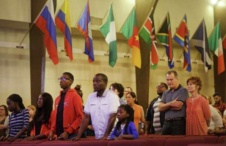 People attend the service at Wilcrest Baptist Church, 10800 Sharpview Dr., Sunday, Aug. 26, 2018, in Houston. Flags are shown through the church representing each countries where the church has sent missionaries.
