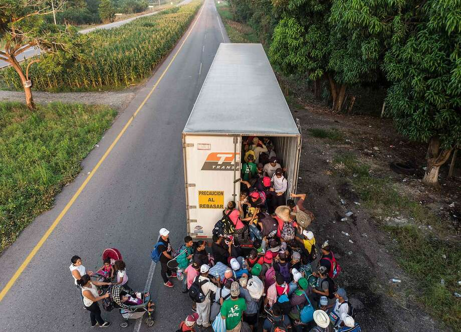 """Honduran migrants crowd into a tractor-trailer near Pijijiapan, southern Mexico, on Oct. 26, 2018. Pentagon is expected to deploy about 800 troops to the Mexico border, after President Donald Trump said the military would help tackle a """"national emergency"""" and called on a caravan of U.S.-bound migrants to turn around. (Photo by Guillermo Arias / AFP/Getty Images) Photo: Guillermo Arias / AFP / Getty Images"""