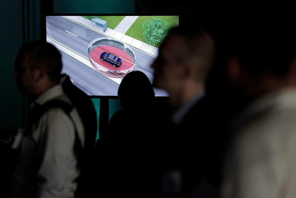 Autonomous vehicle presentations are seen on a screen as attendees listen to a panel discussion during the Smart Mobility Summit at Dogwatch Studios in San Francisco, Calif., on Thursday, October 25, 2018.