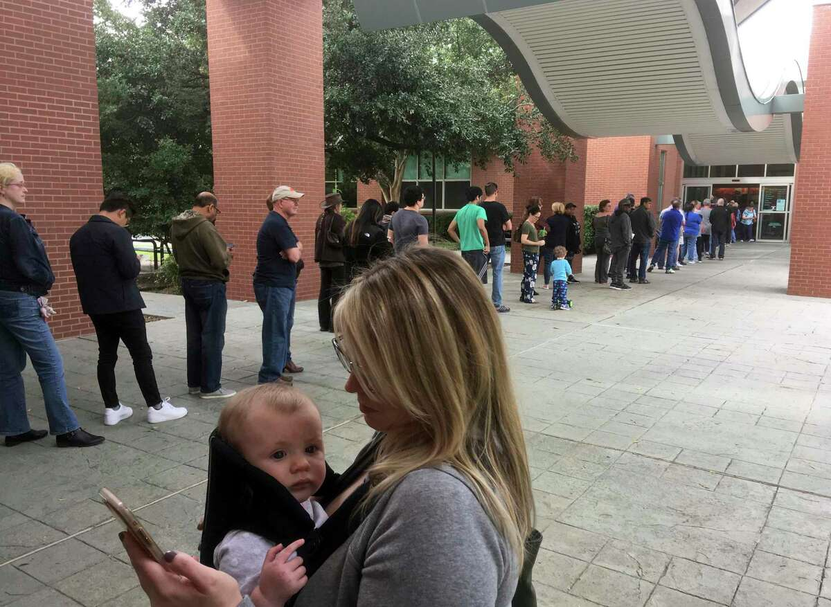 FILE - In this Oct. 22, 2018, file photo, Megan Heckel of Plano holds her daughter Lily as they wait in line for early voting outside Maribelle M. Davis Library in Plano, Texas. Some Texas voters are complaining that while casting Democratic or Republican straight-ticket ballots, voting machines used in 80-plus counties changed their selections to the other party for key races, including the Senate contest between Ted Cruz and Beto O'Rourke. The Secretary of State's office says the problem is occurring on Hart eSlate machines, when voters submit ballots before their choice is fully rendered. It says the machines aren't malfunctioning and instead blames user error. (AP Photo/David Koenig, File)