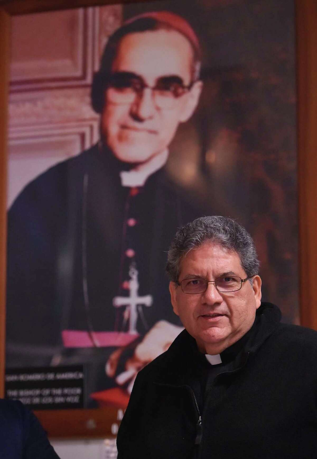 Father Richard Samour, who was baptized in El Salvador by a man who would become a saint, St. Oscar Romero, (in the photograph behind him) a martyr of the Salvadoran civil war.