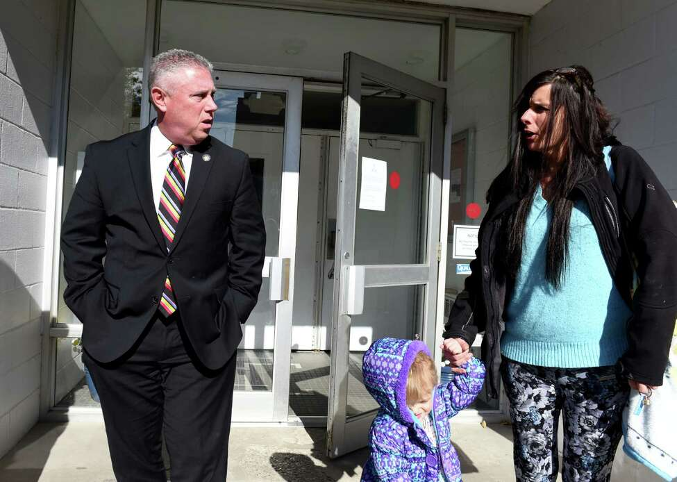 Stacey Avellino, right, speaks to Assemblyman John T. McDonald III, left, after taking her daughter, Lucia, 2, out of daycare at the Cohoes Community Center following its closure on Friday, Oct. 26, 2018. The center is shutting down. (Will Waldron/Times Union)