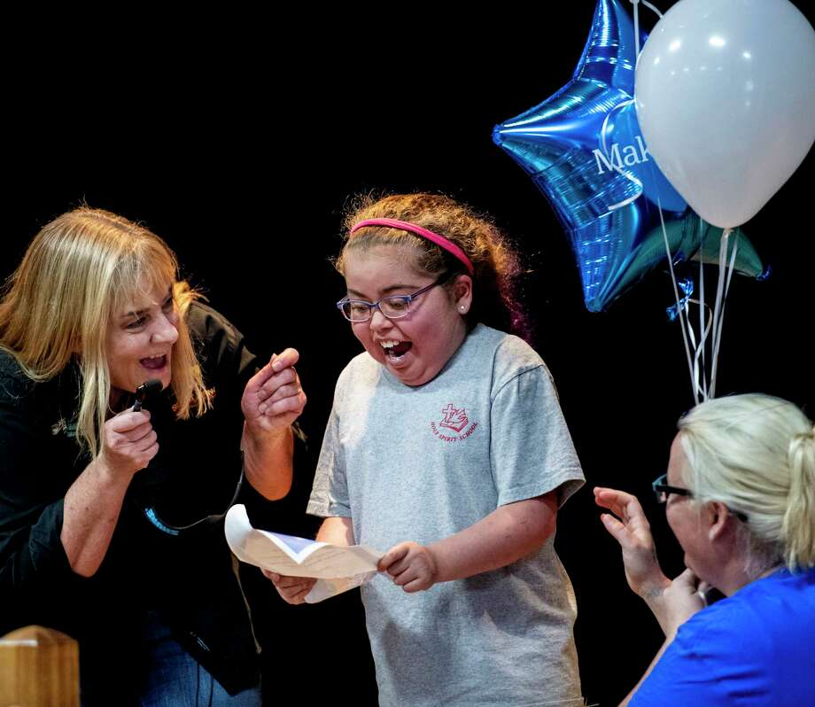 Make-A-Wish recipient Miracle Carter of Stephentown shows her excitement after she learned she was granted her wish to go to Disney World at her school, Holy Spirit School Friday Oct.26, 2018 in East Greenbush, N.Y. Helping to grant her wish are; Trish Marki of the Wildlife Institute of Eastern N.Y., left, and Make-A-Wish volunteer Katie Krays, right.  The wish document was transported by Eurasian Eagle Owl from the Wildlife Institute.  (Skip Dickstein/Times Union) Photo: SKIP DICKSTEIN, Albany Times Union / 40045285A