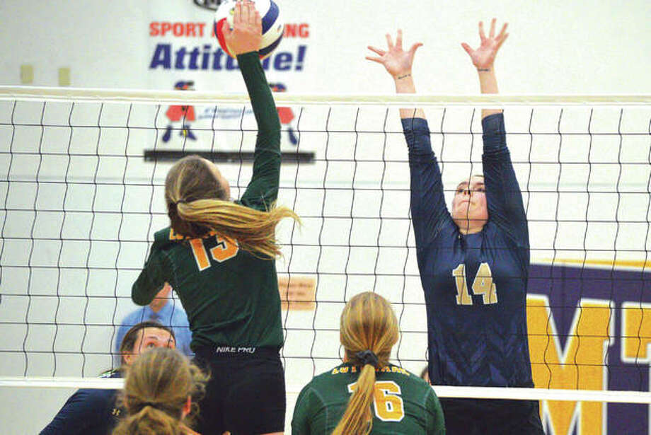 Father McGIvney's Madison Webb, right, goes up to try to block an attempted kill by Metro-East Lutheran's Phoebe Russell during Thursday's championship match at the Class 1A Mount Olive Regional. Photo: Scott Marion/Intelligencer