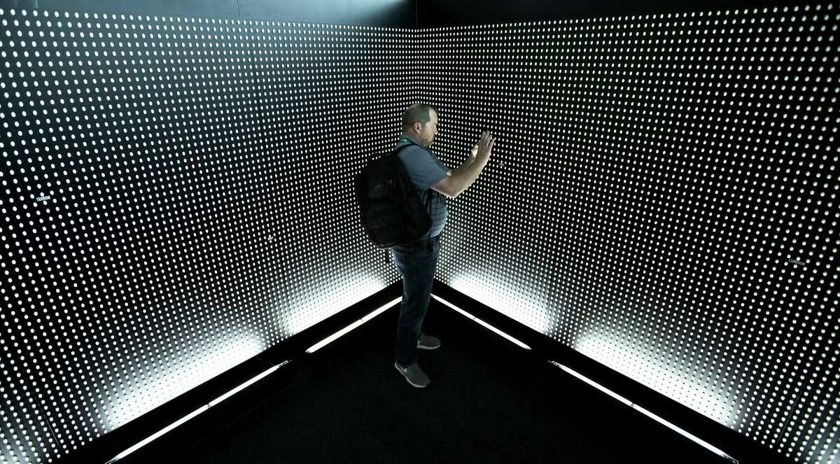 """Tony Bale, of Los Angeles, takes a photo of a pill wall inside the exhibit """"Prescribed to Death"""" at the George R. Brown Convention Center on Tuesday, Oct. 23, 2018, in Houston. The memorial features a wall constructed of 22,000 carved pills, each representing the face of someone who fatally overdosed on a prescribed opioid in 2015. Texas alone lost 1,375 residents to opioid overdose in 2016, comprising nearly 50 percent of all drug overdose deaths among Texans that year."""