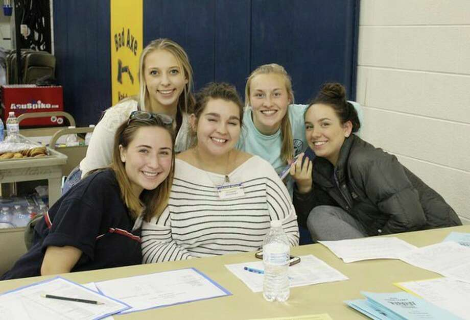 Volunteers from the Bad Axe High School National Honor Society, Jaclyn Iskow, Aryana Peruski, Leeann Murdock, Gabriella Beeler, and Arden Rousseaux help parents, students, and college and military representatives sign in. (Submitted Photo)