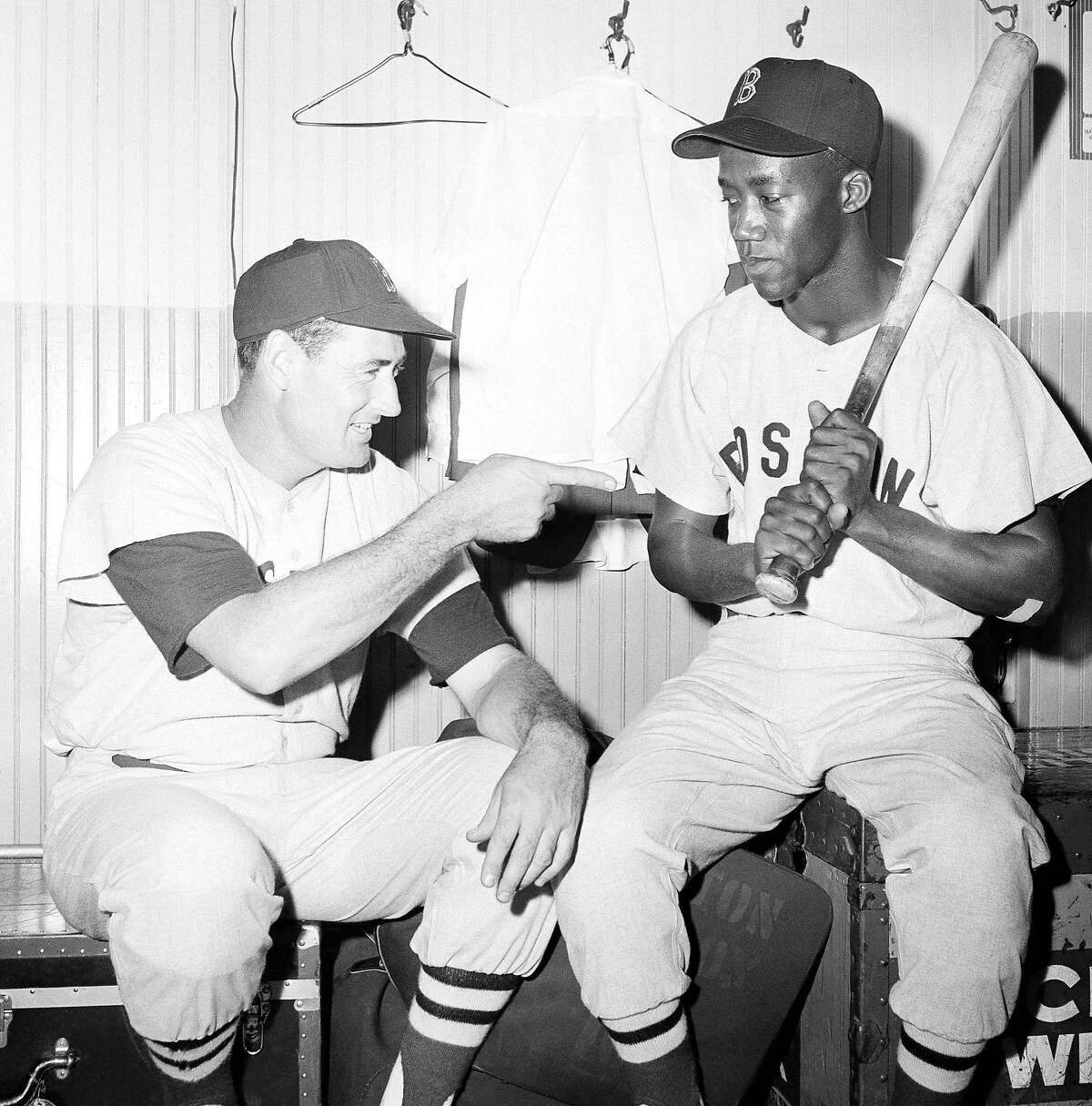 Elijah (Pumpsie) Green, right, an infielder who was recalled from the Minneapolis Farm club to join the Boston Red Sox, is given some friendly tips by Ted Williams, July 21, 1959, Chicago, Ill. Green became the first African American ever to play for the Red Sox. When Green was assigned to the farm club at the start of the season, the Red Sox were subjected to protest from several groups charging discrimination. (AP Photo/Ed Maloney)