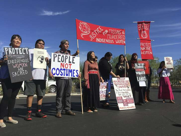 """Native American protesters stand outside the Phoenix office of Yandy.com, a retailer of """"sexy Native American"""" costumes on Wednesday, Oct. 24, 2018. For some ethnic and racial groups, Halloween has long been haunted by costumes that perpetuate stereotypes and instances of cultural appropriation. (AP Photo/Terry Tang)"""