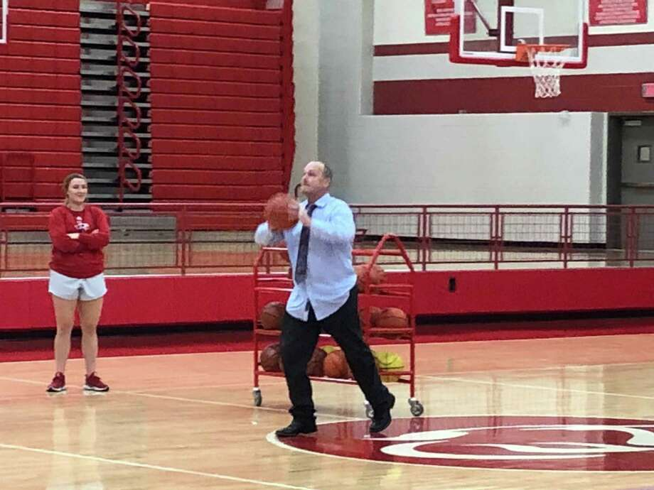 "Crosby ISD superintendent Scott Davis attempts a half-court shot during the ""Thursday Night Madness"" girls basketball showcase on October 25 Photo: Elliott Lapin / Staff Photo"