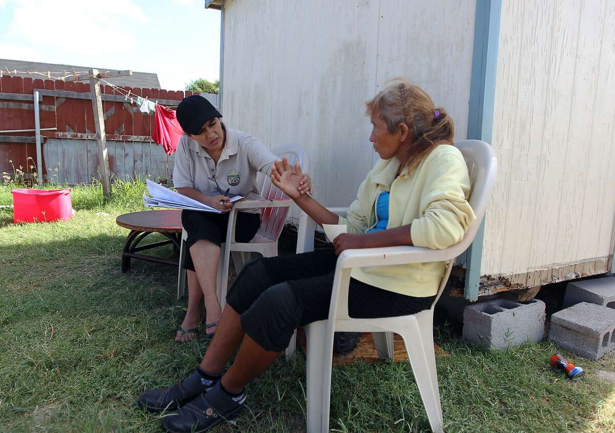 Promotora Elida Perez (left) inspects the hand of Giorgina de Rocha in the North San Carlos colonia in Edinburg in 2012. Texas needs to look at more than just the infrastucture needs of Texas colonias.