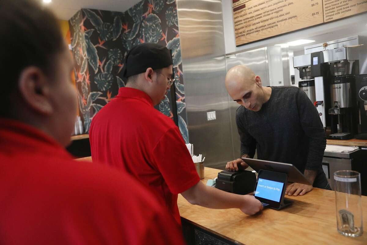 Matt (right), one of the three co-owners of Mateo's, uses a Square Register to check out a customer at Mateo's on Market Street on Thursday, October 25, 2018 in San Francisco, Calif.