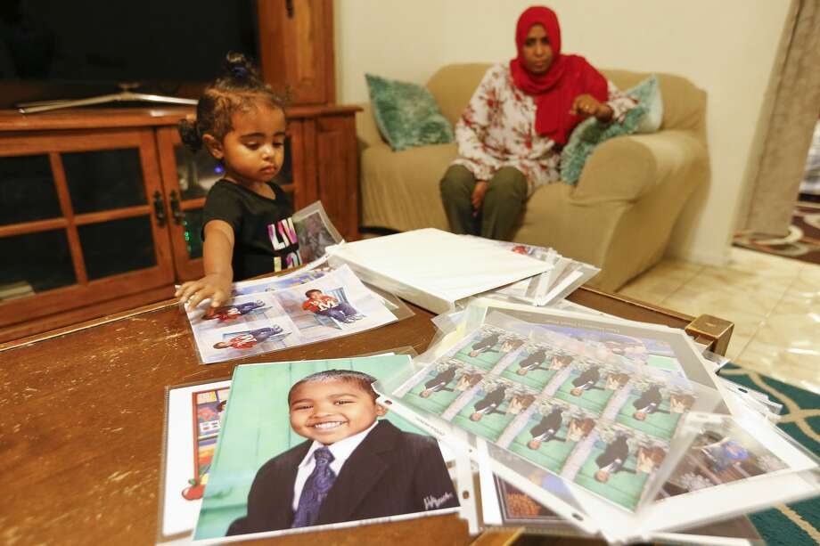 Rahuf Abdalla, 2, looks through a photo album of her brother as her mother, Wigdan Ahmed Mohammed, watches her in their home in Houston. Her brother, Mohammed Ali Abdalla, died 2 years ago after he was hit in a crosswalk. He was 4 years old. Photo: Steve Gonzales/Staff Photographer