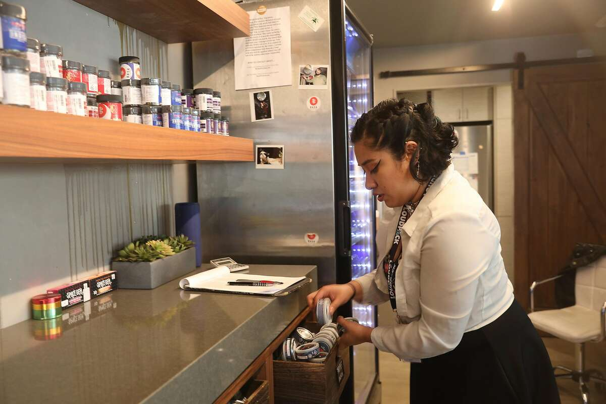Kat Flores, a marijuana bud tender, selects a container of flowers for a customer at BASA Collective on Thursday, October 18, 2018 in San Francisco, Calif.