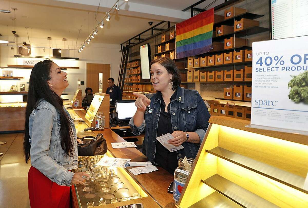 Christine Brizendine buys some products from Dannie Holzer, Member Consultant, right, at Sparc dispensary in San Francisco, Calif., on Tuesday, June 26, 2018. New regulations for recreational Marijuana packaging take effect on July 1, and sellers are moving non-conforming products in anticipation of the changes.