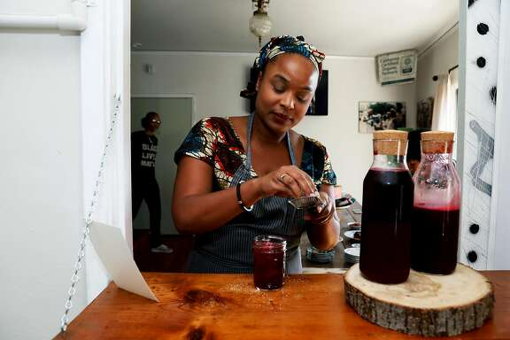 Chef Monifa Dayo scrapes nutmeg as she makes a glass of Bissap prior to the start of a party at her apartment in Oakland, Calif., on Saturday, October 20, 2018. The drink contains Senegalese Bissap flowers, honey, key lime, ginger and nutmeg.