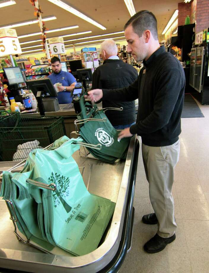 """Grocery Manager Anthony Caponera puts out re-usable bags instead of the single-use ones as part of Milford's """"Green Halloween"""" effort at Adams Supermarket in Milford, Conn., on Friday Oct. 26, 2018. The bags will be used starting tomorrow and for the rest of the week. Photo: Christian Abraham / Hearst Connecticut Media / Connecticut Post"""