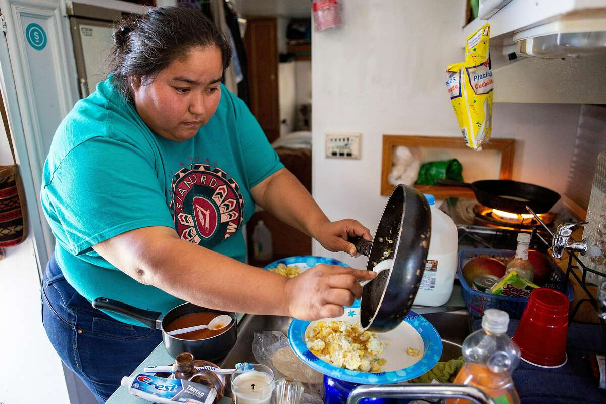 Erika makes eggs, beans and tortillas for breakfast in her RV in the Bayview neighborhood on Wednesday, Oct. 17, 2018, in San Francisco, Calif.